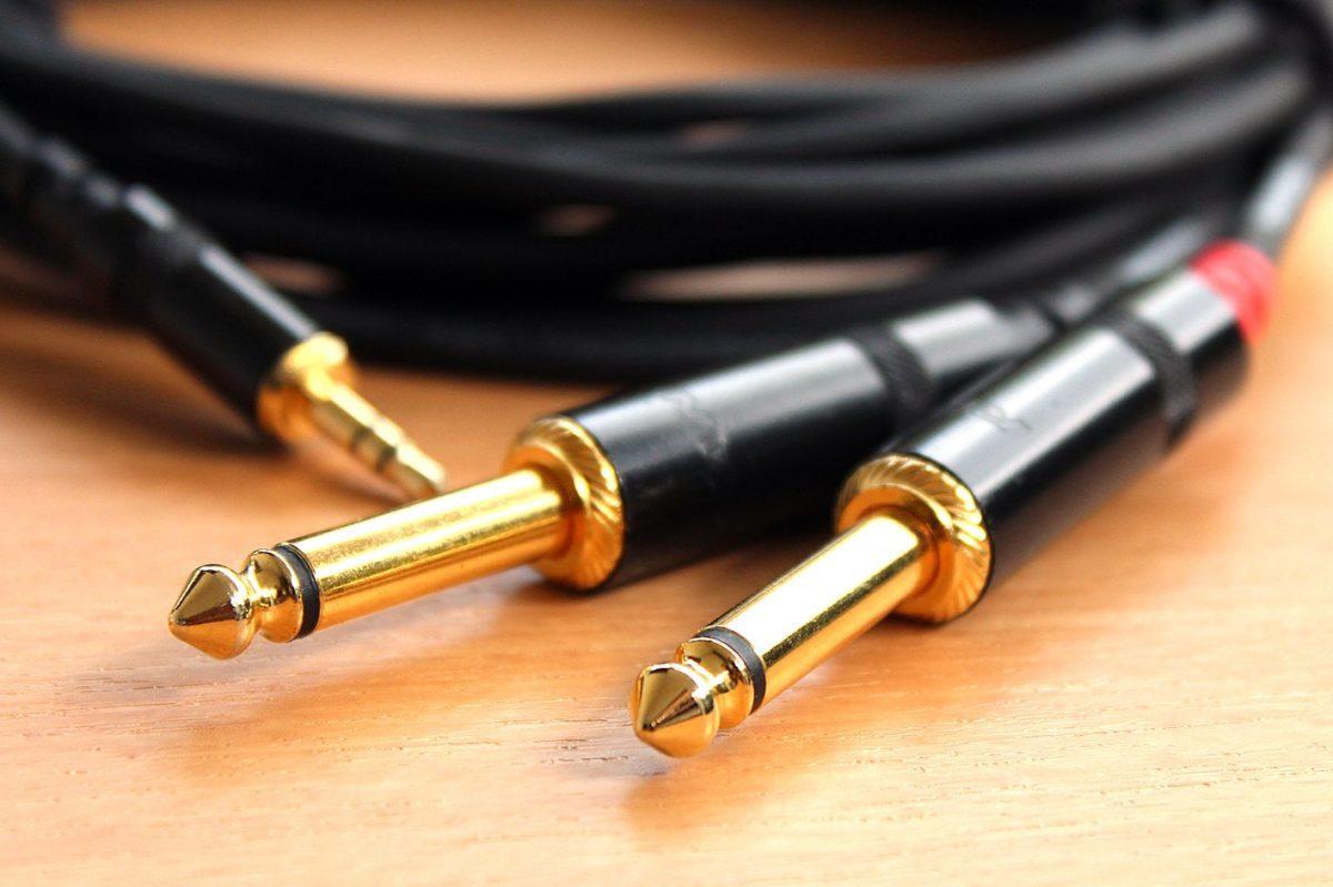 Vergoldete Klinkenstecker und Stereo-Miniklinke im Hintergrund